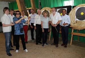 Das Bild zeigt einen Bogenschützen mit Pfeil und Bogen in den Händen. Er trägt Kopfhörer. Eine weitere Person assistiert ihm. Auch er hat Kopfhörer auf. Weitere Personen stehen im Hintergrund nebeneinander vor mehreren Zielscheiben.