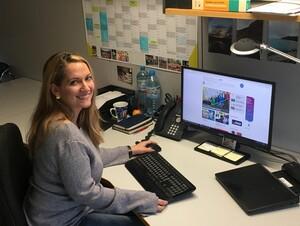Bettina Andres sitzt an ihrem Arbeitsplatz. Sie hat die linke Hand an der PC-Maus und schaut über ihre rechte Schulter.