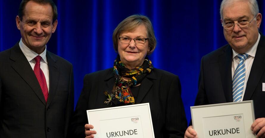 Alfons Hörmann (li.) gratuliert den neuen DOSB-Ehrenmitgliedern Ilse-Ridder-Melchers und Hans-Peter Krämer. Foto: Ronald Bonss