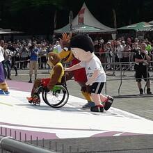 Taffi, das Maskottchen des Kinderturnens der Deutschen Turnerjugend, sitzt im Rollstuhl und wird von den Maskottchen des DOSB und der Deutschen Schützenjugend eine Rampe hoch geschoben. Im Hintergrund schauen viele Zuschauer/innen dabei zu.