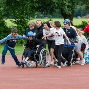 Eine Gruppe aus Mädchen und Jungen auf einer Leichtathletikbahn, einige davon im Rollstuhl. Foto: Eugen Bebhardt