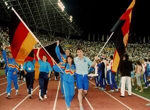 Arm in Arm ziehen die Fahnenträger Gabriele Lippe aus der Bundesrepublik und Ulf Timmermann aus der DDR am 1.9.1990 bei der Schlussfeier der Leichtathletik-Europameisterschaft im jugoslawischen Split in das Stadion ein. Bei dem Championat gingen letztmalig deutsche Sportler*innen bei großen Wettkämpfen in zwei getrennten Mannschaften an den Start. Foto: picture-alliance
