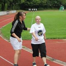 Eine engagierte junge Frau unterstützt das gemeinsame Sporttreiben von Menschen mit und ohne Behinderung.