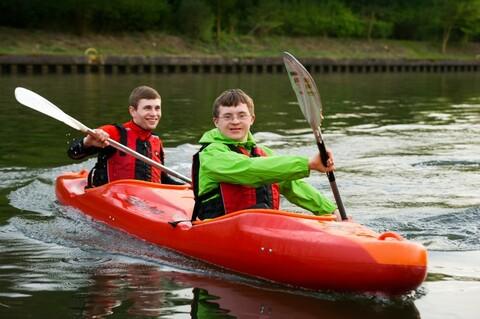 Zwei junge Männer sitzen in einem Kajak und paddeln.