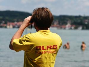 Ein Rettungsschwimmer wacht über Badende in einem See. Foto: picture-alliance