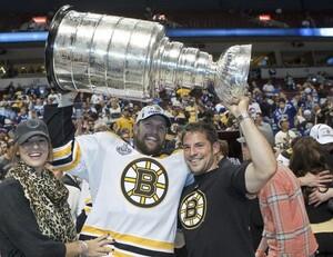Dennis Seidenberg stemmt stolz den Stanley-Cup. Mit ihm freuen sich seine Ehefrau Rebecca und sein Bruder Yannic. Foto: picture-alliance