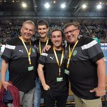 Vier Blindenreporter, die bei der DHM im Einsatz sind, stehen dicht nebeneinander. Im Hintergrund ist eine Sporthalle mit einer Zuschauertribüne zusehen. Auf dem Spielfeld sind Sportler aktiv.