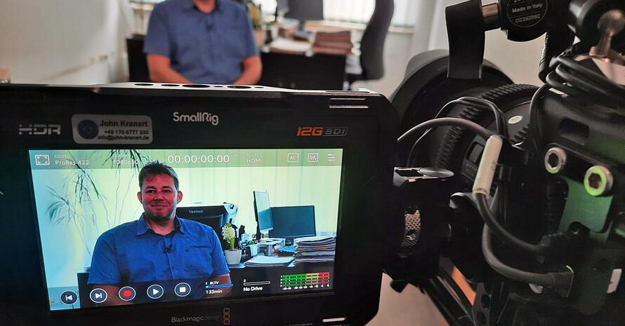 Eine Kamera mit ausgeklapptem Bildschirm nimmt einen Mann auf, der auf einem Stuhl in einem Büro sitzt.