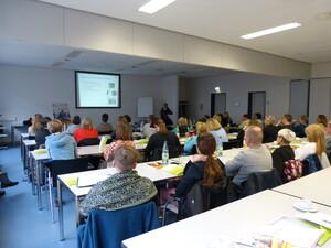 In einem Seminarraum sitzen viele Menschen in Reihen an Tischen. Eine Person trägt etwas mit einer Präsentation vor.