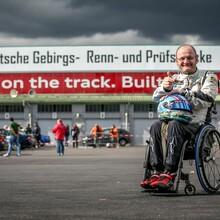 Gustav Engljähringer steht mit seinem Rollstuhl auf der Strecke. Er hat einen Helm auf dem Schoß und hält den Daumen hoch.