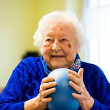 Eine ältere Dame hält einen Gymnastikball in den Händen und lacht.