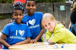Ein junge blonde Frau ohne Unterarme schreibt etwas auf. Zwei Kinder im Sportdress schauen ihr zu.