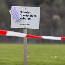 """Ein Schild mit der Aufschrift """"Betreten des Sportplatzes verboten"""" steht auf einem Rasenplatz. An dem Schild hängt eine Mund-Nasen-Schutzmaske"""