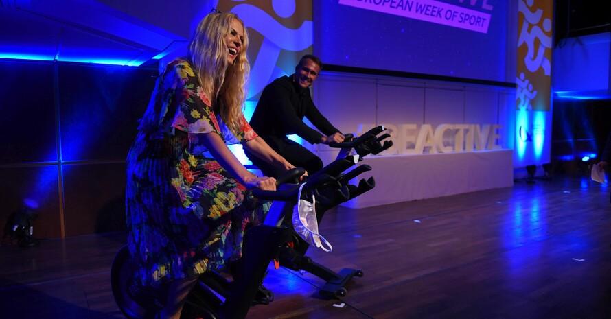 Die Botschafter*in der Europäischen Woche des Sports, Yoga-Expertin und Fernsehmoderatorin Sonya Kraus und Judo-Weltmeister Alexander Wieczerzak zeigten auf dem Fahrrad-Ergometer, wie fit sie sind. Foto: EU