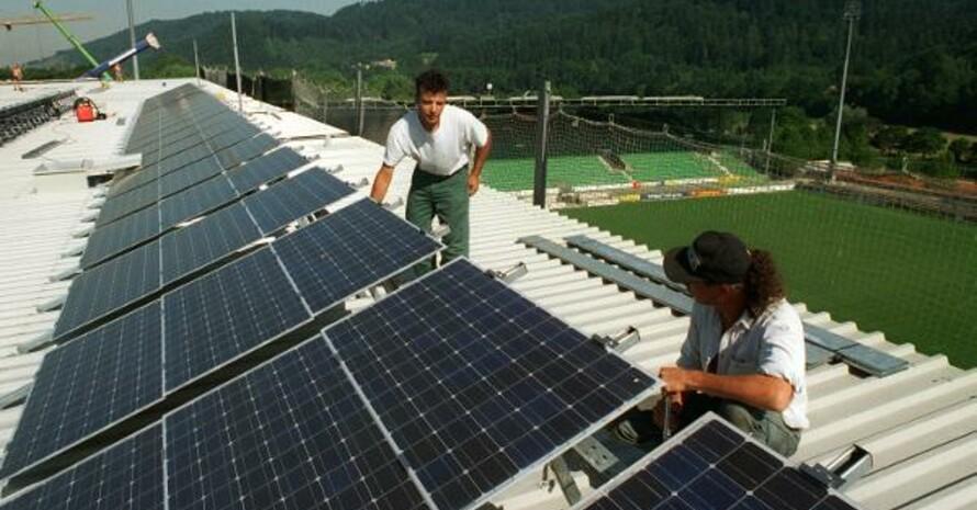 Arbeiter installieren am Stadion des SC Freiburg eine Solaranlage. Foto: picture-alliance