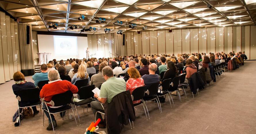 Ein Saal, in dem viele Menschen in Reihen auf Stühlen sitzen, mit Bühne, auf der gerade eine Person eine Präsentation vorstellt.