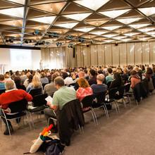 In einem großen Saal sitzen viele Menschen in Stuhlreihen und verfolgen eine Präsentation.