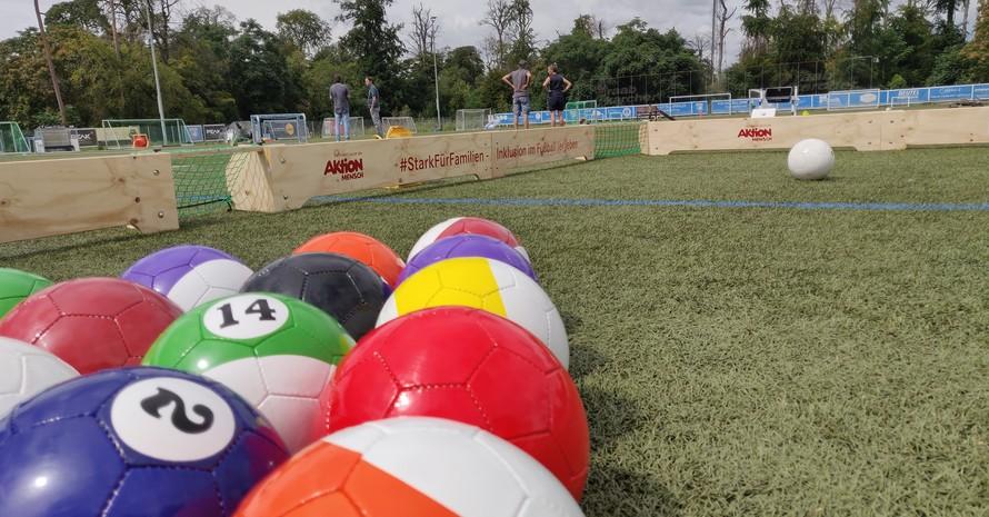 Billardbälle in Fußballgröße liegen als Dreieck auf einem Fußballplatz. Ein Feld ist mit langen schmalen Holzplatten begrenzt. Dazwischen sind ganz kleine Tore.