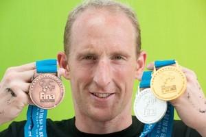 Thomas Lurz präsentiert stolz seinen kompletten Medaillensatz von der WM 2011 in Shanghai. Foto: picture-alliance