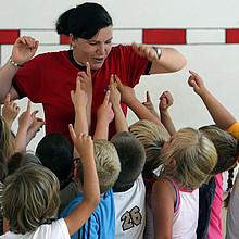 Übungsleiterin mit Kindern. Foto: picture-alliance
