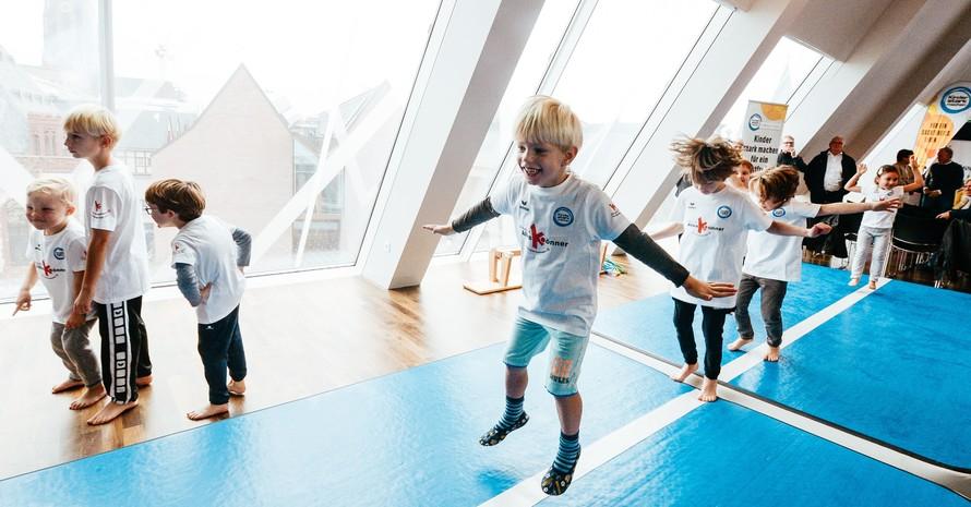 """Kinder turnen mit viel Spaß bei der Aktion """"Kinder stark machen"""". Foto: picture-alliance"""
