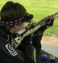 Natascha Hiltrop stützt sich mit beiden Ellenbogen am Schießtisch ab. Sie schießt mit einem Gewehr und trägt eine Schirmmütze.