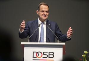 DOSB-Präsident Alfons Hörmann spricht von einem Stehpult mit DOSB-Logo und hebt dabei beide Hände