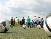 Auf einem Rasenplatz stehen Sportlerinnen und Sportler mit Abstand im Kreis. Einige tragen Orthesen. Es liegen Fußbälle auf dem Rasen.