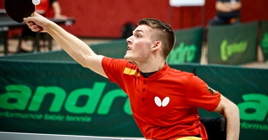 Ein im Rollstuhl sitzender Tischtennisspieler, der die rechte Hand mit Schläger richtung Ball ausstreckt.