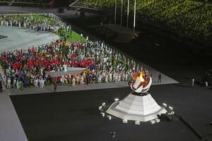 Athlet*innen der teilnehmenden Nationen in Tokio versammeln sich bei der Abschlussfeier im Olympiastadion vor der Olympischen Flamme, bevor sie erlicht. Foto: picture-alliance