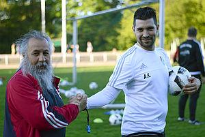 """Der Trainer des SV Türkgücü-Ataspor, Alper Kayabunar, begrüßt einen der treusten Fans. """"Ibo"""" verteilt beim Training Trinkflaschen und hat den Medizinkoffer parat. Foto: DJS/Länge"""