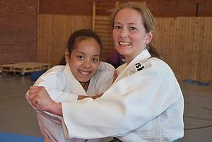 Ein Mädchen und eine Frau beim Judo. Sie tragen weiße Anzüge und lachen.
