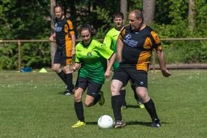 Männer und Frauen spielen auf Rasenplatz Fußball