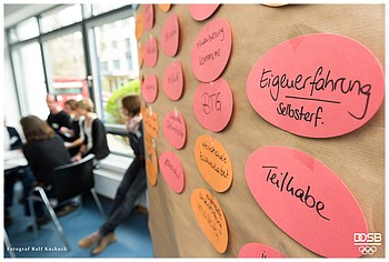 """Im Vordergrund steht eine Pinnwand mit Karten auf denen Worte wie""""Teilhabe"""", """"Eigenerfahrung"""" stehen, im Hintergrund sieht man Seminarteilnehmer/innen"""