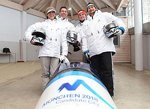 Die Kuratoriumsvorsitzende und der Geschäftsführer von München 2018 rasten im Bob talwärts zur Siegerehrung des Rodelweltcups.