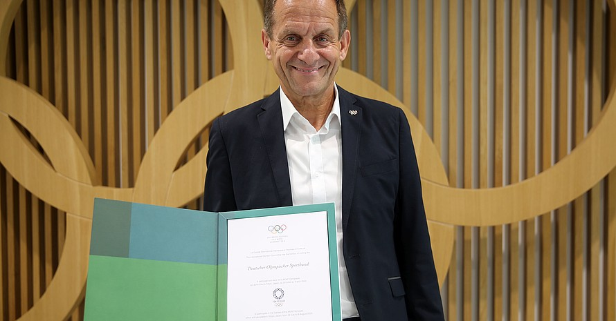 Alfons Hörmann zeigt die offizielle Einladung des IOC an den DOSB zu den Olympischen Spielen 2020 in Tokio. Foto: DOSB