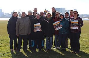 Eine Gruppe aus Männern und Frauen steht auf einer wiese, einige halten das Handbuch hoch
