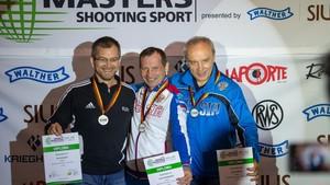 Drei Männer halten eine Urkunde in der Hand, tragen eine Medaille um den Hals und lachen.