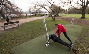 Zwei Männer trainieren an der Station eines Fitnessparcours an der Alster in Hamburg. Foto: picture-alliance