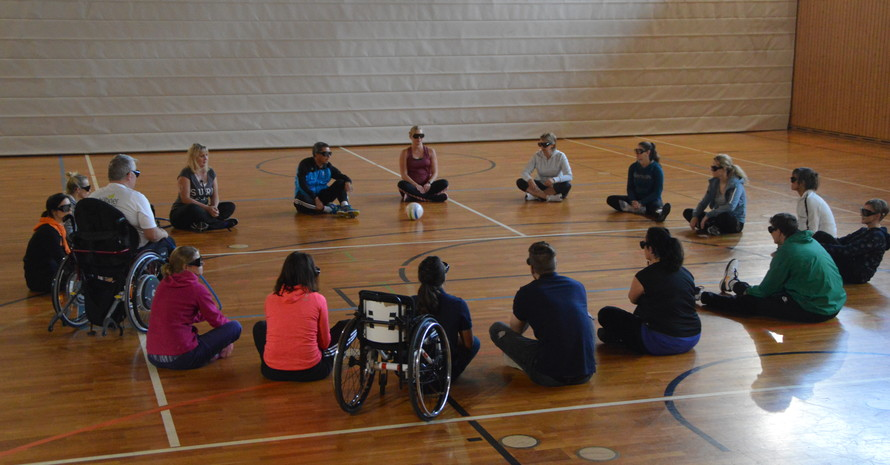 Die Teilnehmerinnen und Teilnehmer sitzen in einem Kreis in einer Sporthalle. Alle tragen Simulationsbrillen.