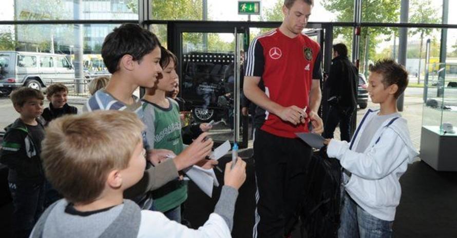 Manuel Neuer schreibt Autogramme für seine jungen Fans. Foto: picture-alliance