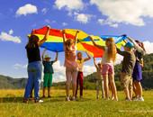 Kinder stehen im Kreis auf der Wiese und schwingen ein buntes SChwungtuch in die Höhe.