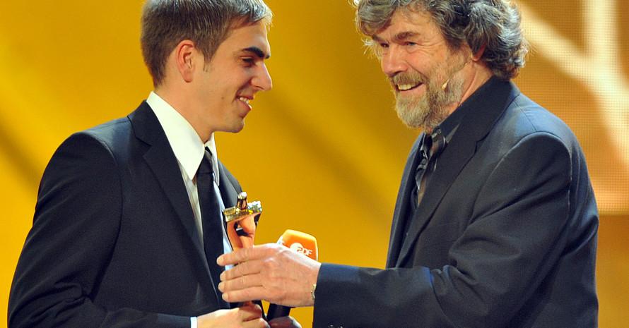 """Reinhold Messner (r.) gratuliert dem Kapitän der Fußball-Nationalmannschaft Philipp Lahm zur Auszeichnung """"Sportler des Jahres"""". Foto: picture-alliance"""