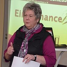 Marion Böhm hält einen Vortrag. Im Hintergrund ist eine Power-Point-Präsentation zu sehen. Sie zeigt den Daumen hoch. In der anderen Hand hält sie ein Papier nach unten.