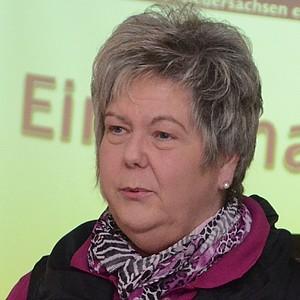 Marion Böhm hält einen Vortrag. Im Hintergrund ist eine Power-Point-Präsentation zu sehen.