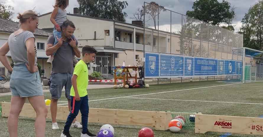Eine Frau, ein Mann, der ein Kind auf den Schultern trägt, und ein anderes Kind stehen auf einem Fußballfeld. Es gibt eine Begrenzung aus Holz. Es sind große Billardkugeln zu sehen.