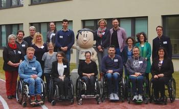 Gruppenfoto der Sport-Inklusionsmanger/innen und Mitarbeiter/innen des DOSB. In der Mitte ist das Maskottchen Trimmi, in der ersten Reihe sind sechs Rollstuhlfahrer/innen