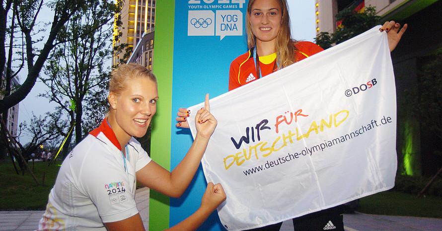 Beachvolleyballerin Lisa Arnholdt (re.) trägt die deutsche Fahne. Partnerin Sarah Schneider freute sich mit ihr.