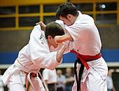 Zwei Judoka im weißen Anzug kämpfen gegeneinander in einer Sporthalle.