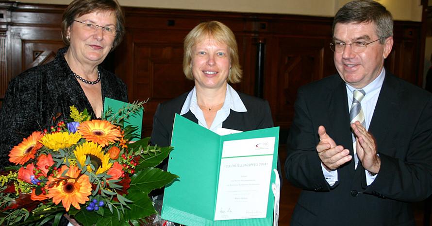 Marlis Gebbing (m.) erhält den Preis von Ilse Ridder-Melchers und Thomas Bach.